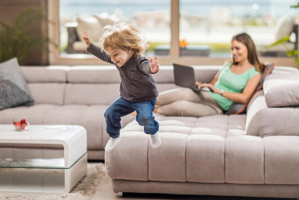 Glad pojke hoppar från soffan hemma. Hans mamma använder en laptop i bakgrunden.